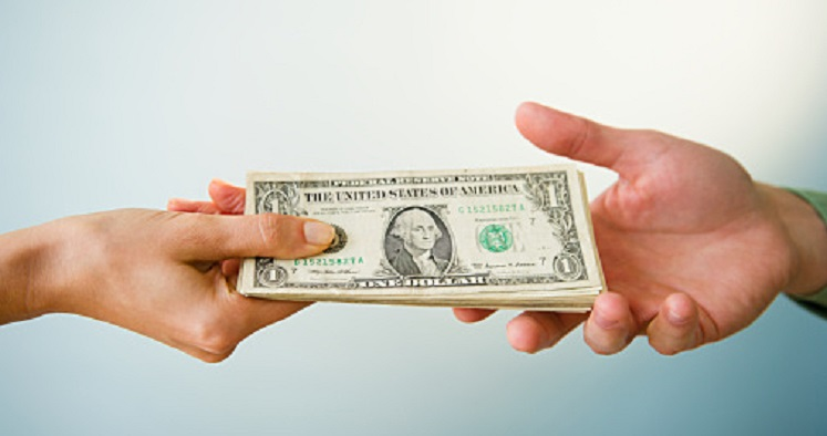 Close up of man's and woman's hands holding banknotes, studio shot